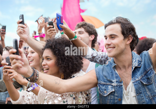 Fans with camera phones cheering at music festival - Stock Image