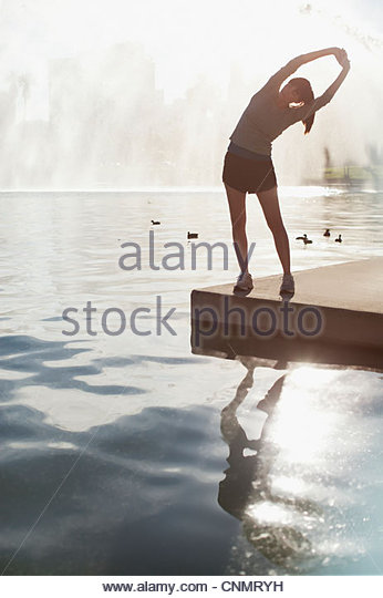 Woman stretching by still lake - Stock-Bilder