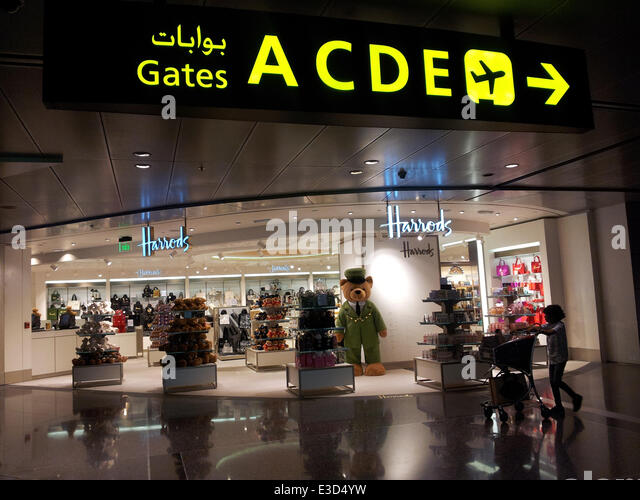 A lad pushing a trolley walks past The Harrods Store at the new ​​​Hamad International Airport (HIA) in Doha. Credit: - Stock Image