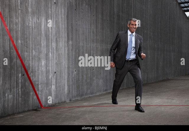 businessman crossing red line - Stock Image