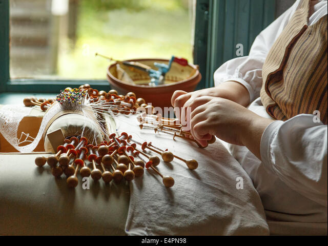 Bobbin lace being produced with the traditional method by hand with bobbins and a pillow with pins guiding the pattern. - Stock-Bilder
