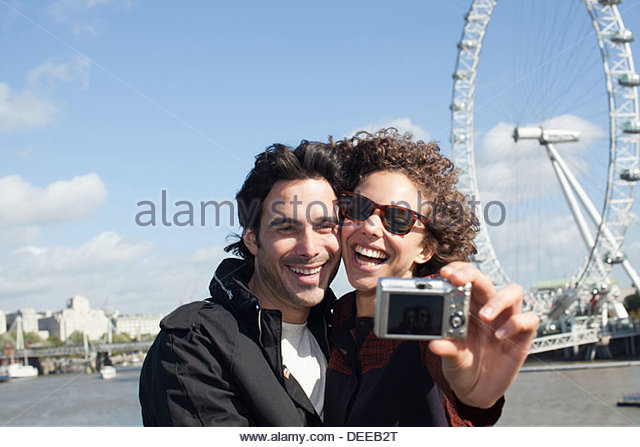 Happy couple taking self-portrait with digital camera near ferris wheel - Stock Image