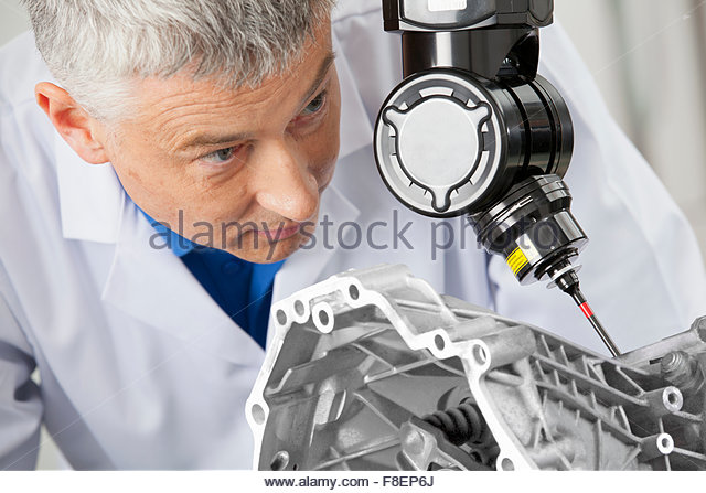Close up of engineer using computer controlled probe to scan engine block - Stock Image