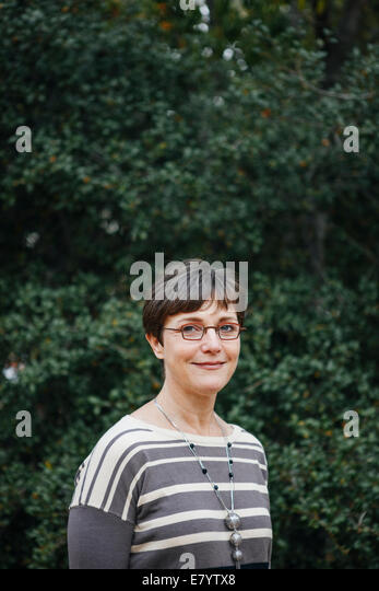 Woman against background of tree foliage - Stock Image