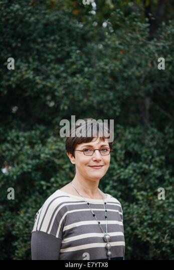 Woman against background of tree foliage - Stock-Bilder