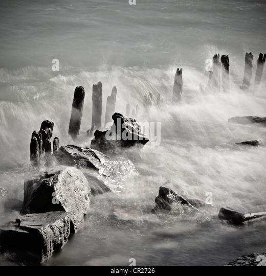 Waves breaking over wood piles - Stock Image