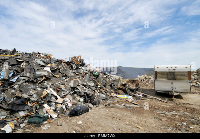 Waste Management landfill in Bourne, Massachusetts with commercial construction debris and old travel trailer USA. - Stock Image