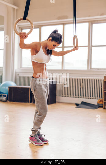 Fit woman using gymnast rings as part of a workout at the gym. Muscular young female athlete exercising with rings. - Stock Image