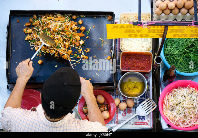Kota Kinabalu, Malaysia - August 1, 2017: Top view of unidentified man cooking a fried radish turnip with vegetables - Stock Image