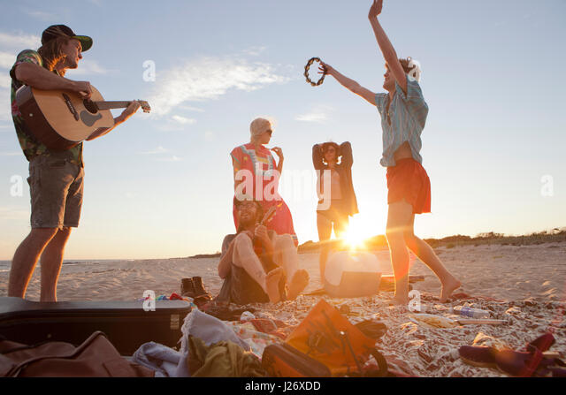 Friends playing music together on a beach - Stock Image