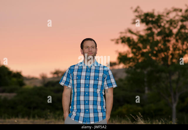 Man with hands in his pockets at sunset looking off to the right. - Stock Image