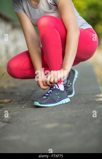 Closeup young sporty girl tying shoelaces on sneakers outdoors. - Stock Image
