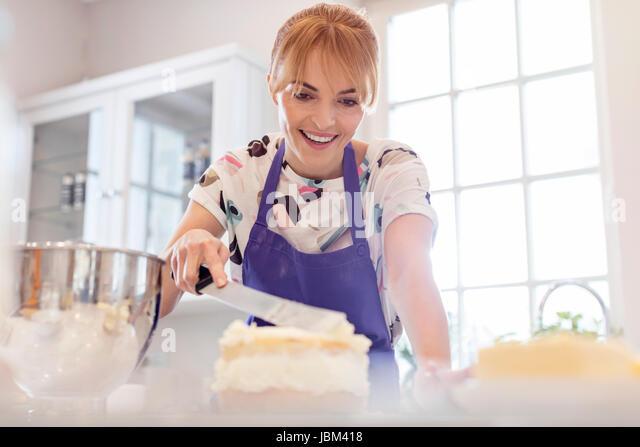Smiling woman baking, icing layer cake in kitchen - Stock-Bilder