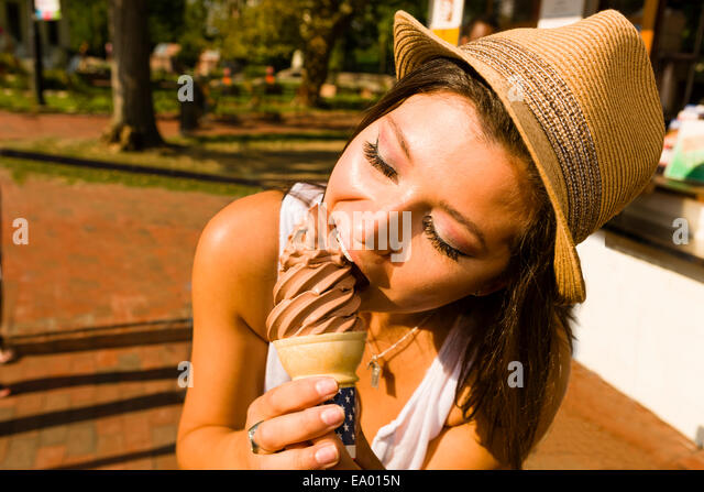 Young woman eating ice cream cone in park - Stock Image