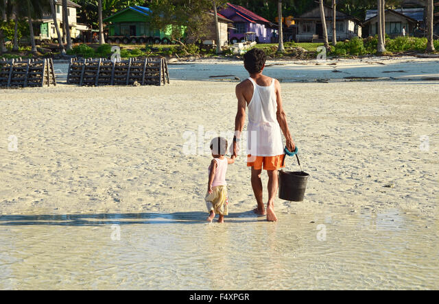 Man and son walk on the beach - Stock Image