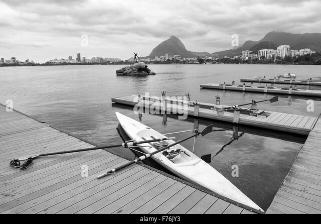 Rowing boat with oars docked at a wood pier on the Lagoa Rodrigo de Freitas lagoon with a view of Rio de Janeiro - Stock Image