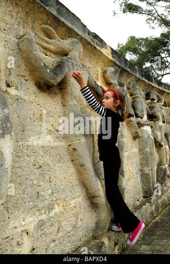 Child (6 years old) inspecting limestone sculptures. Kings Park, Perth, Western Australia, Australia - Stock Image
