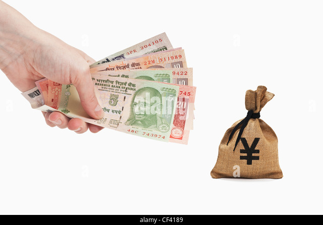 Many diverse Indian rupee bills are held in the hand. Near by is a money bag with a Japanese Yen currency sign. - Stock-Bilder