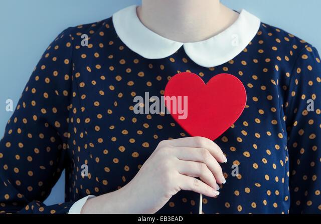 Woman wearing polka dot dress holding heart shape object - Stock Image