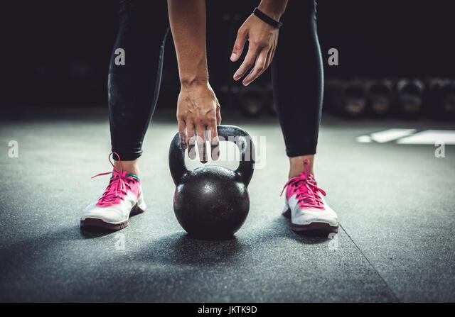 Woman inside at gym working out with a kettlebell. - Stock Image