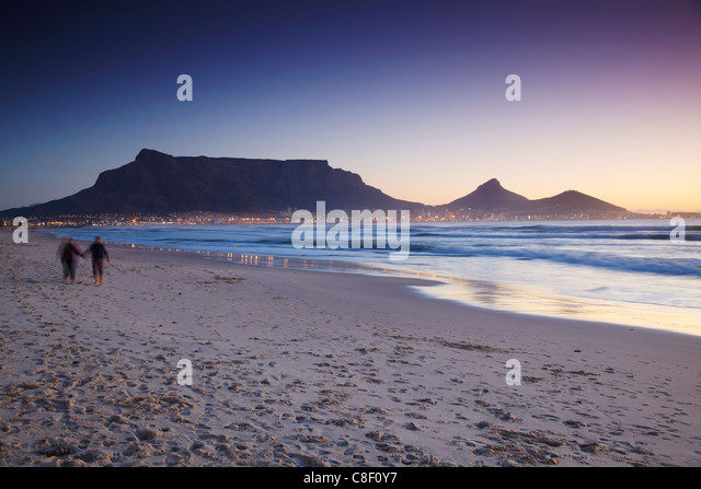 People walking on Milnerton beach with Table Mountain in background, Cape Town, Western Cape, South Africa - Stock Image