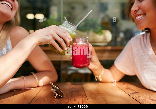 Close up shot of female friends toasting juice glasses at sidewalk cafe. Two happy women enjoying fresh drinks at - Stock Image