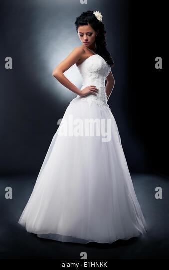 One beautiful fiancee in marital white dress posing in studio - series of photos - Stock Image