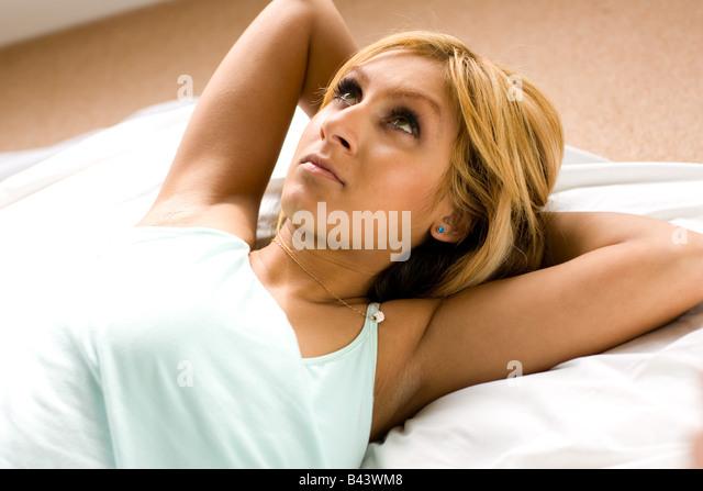 Worried girl lying on bed - Stock Image