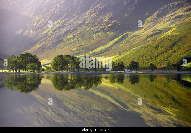 reflections on the shore of Buttermere at dawn, Cumbria, Lakes District, Cumbria, England, UK - Stock Image