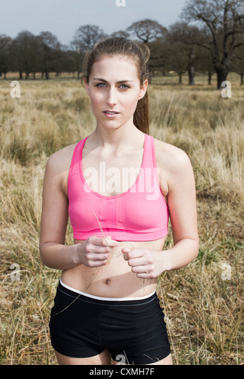 Woman in sports clothing in a park portrait - Stock Image