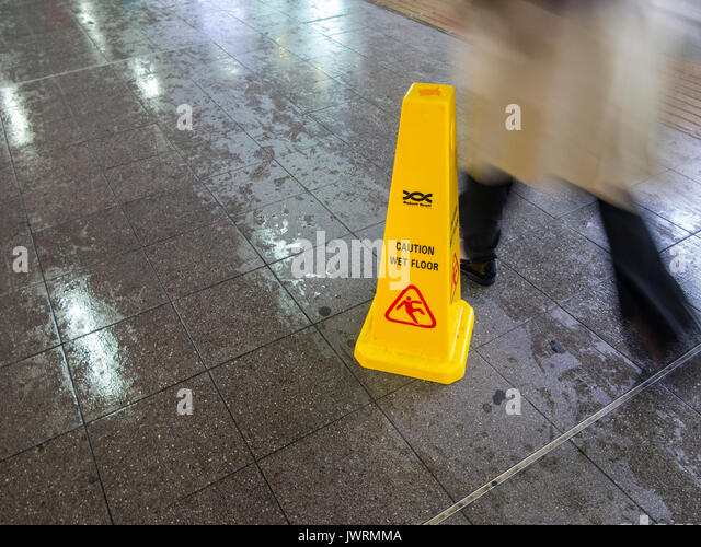 People walking past a Caution Wet Floor sign at a station - Stock Image