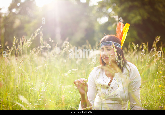 Mature woman in native american headdress in long grass - Stock Image