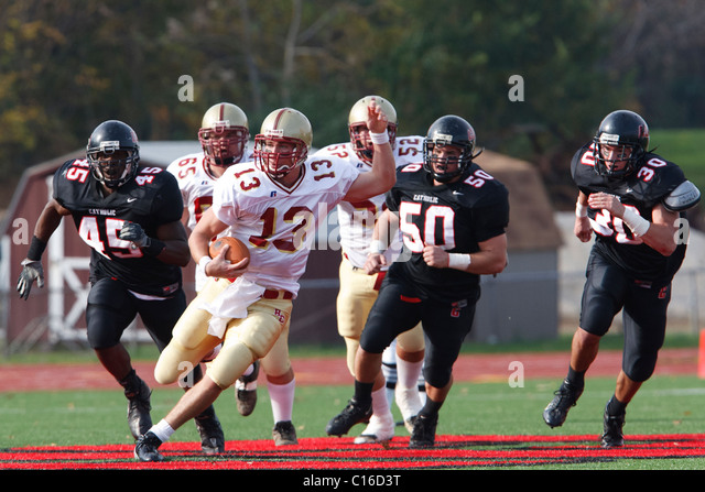 Bridgewater College quarterback rushes the ball against Catholic University during a college football game. - Stock Image