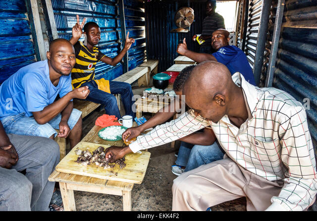 South Africa African Johannesburg Soweto Black man friends eating lunch - Stock Image
