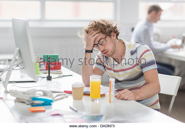 Young man with head in hands in creative office - Stock-Bilder