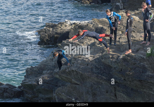 Group of teenagers tombstoning off cliffs on the headland in newquay