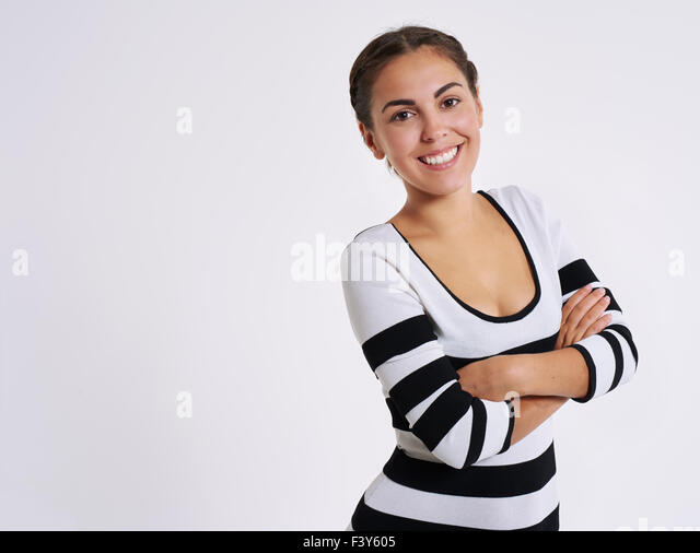 Vivacious confident pretty young woman standing with folded arms giving the camera a lovely smile, upper body on - Stock Image