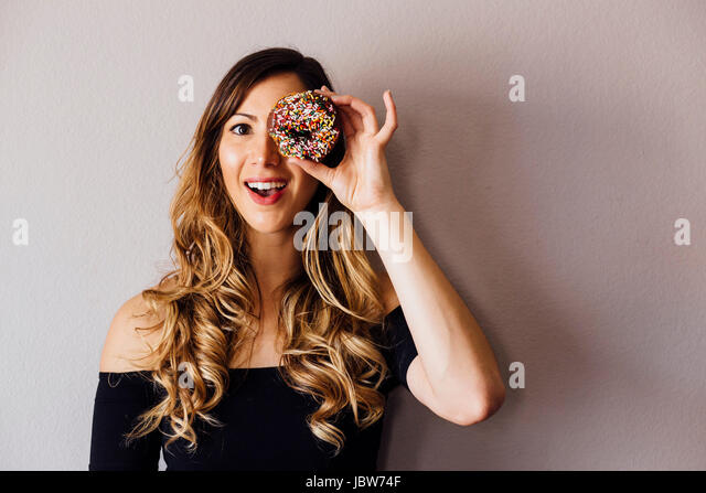 Portrait of young woman with long blond hair holding doughnut hole over eye - Stock-Bilder