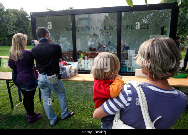 Duisburg Loveparade 2010: Glass cube at the site of the tragedy in which sorrow gifts, candles and toys are kept - Stock Image