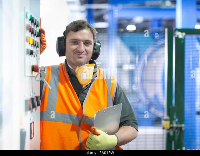 Worker at controls of metal ore grinding mill - Stock-Bilder