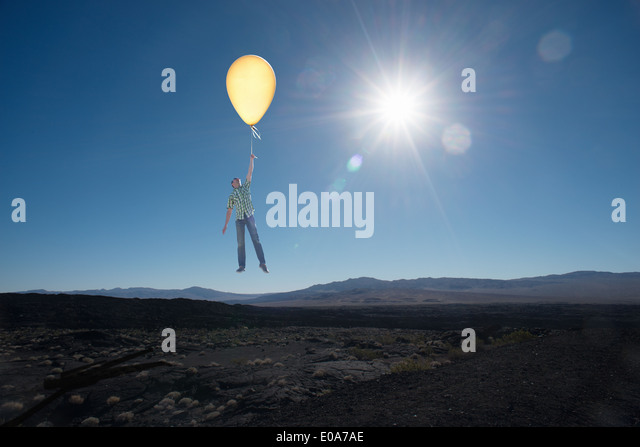 Mid adult man floating with balloon in desert - Stock Image