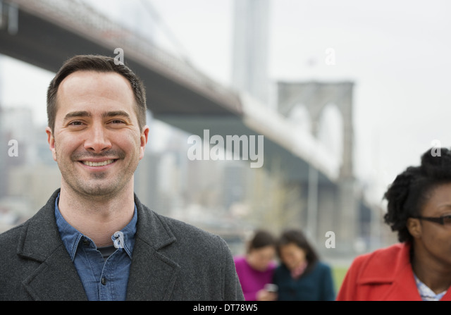 crossing over the East River.  Four people, two women looking at a smart phone, and a man and woman in the foreground. - Stock Image