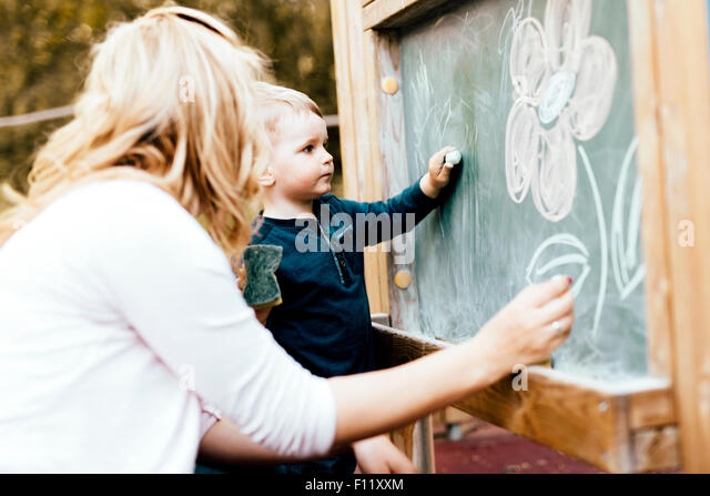 Beautiful mother and son drawing on blackboard with chalk - Stock-Bilder
