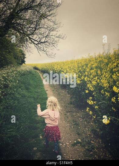 Young child walks by an oil seed rape field - Stock Image