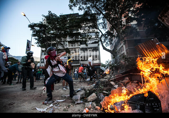 Caracas, Venezuela. 3rd Mar, 2014. Demonstrators throw rocks in a clash against the Bolivarian National Police during - Stock Image