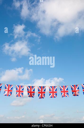 Bunting with Union Jack UK flag against blue sky - Stock Image