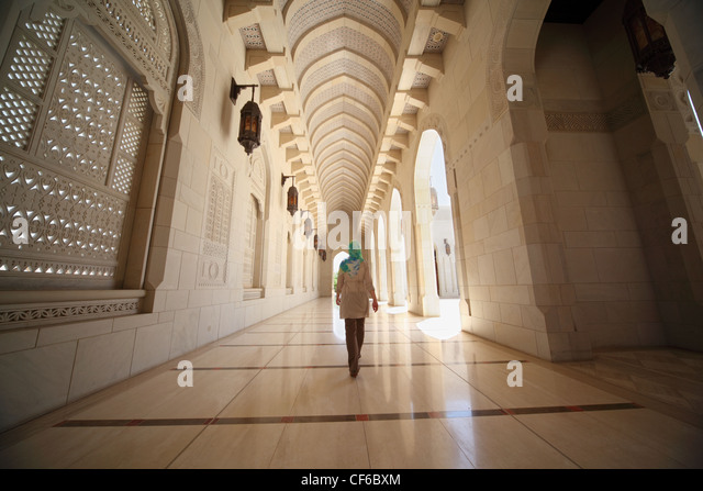 woman with kerchief walking in corridor inside Grand Mosque in Oman. Wide Angle. - Stock Image