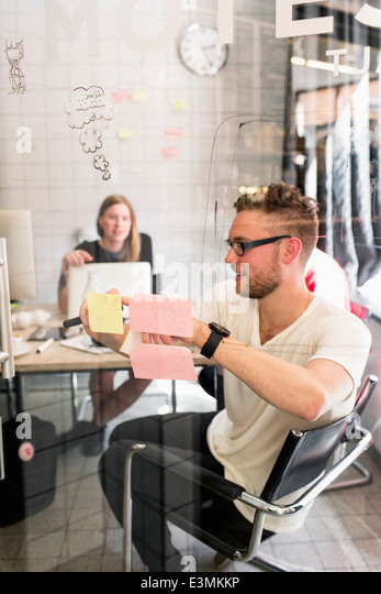 Young businessman writing ideas on adhesive notes with female colleague in background at new office - Stock Image