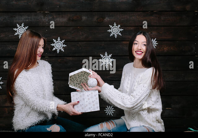 Two young girls holding bright holiday present - Stock Image