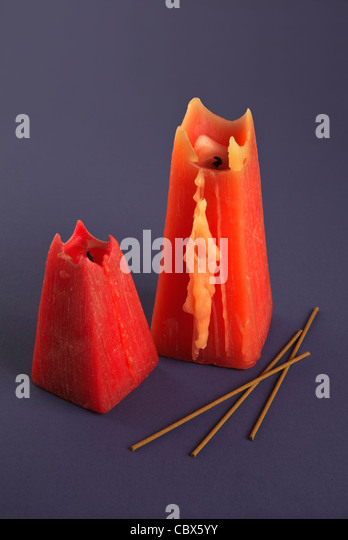 Two red Candles and incense sticks on blue background - Stock Image